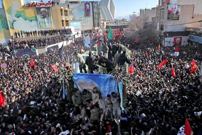 "Coffins of Gen. Qassem Soleimani and others who were killed in Iraq by a U.S. drone strike, are carried on a truck surrounded by mourners during a funeral procession, in the city of Kerman, Iran, Tuesday, Jan. 7, 2020. The leader of Iran's Revolutionary Guard threatened on Tuesday to ""set ablaze"" places supported by the United States over the killing of a top Iranian general in a U.S. airstrike last week, sparking cries from the crowd of supporters of ""Death to Israel!"" (Erfan Kouchari/Tasnim News Agency via AP)"
