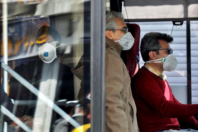 A public bus driver, right, and commuters wear masks to help guard against the Coronavirus in downtown Tehran, Iran, Sunday, Feb. 23, 2020. On Sunday Iran's health ministry raised the death toll from the new virus to 8 people in the country, amid concerns that clusters there, as well as in Italy and South Korea, could signal a serious new stage in its global spread. (AP Photo/Ebrahim Noroozi)