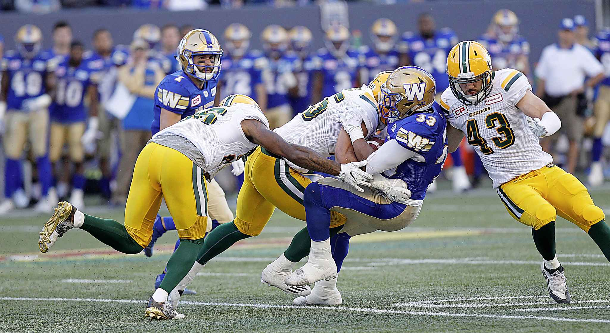 Winnipeg Blue Bombers' Andrew Harris goes down under a crowd of Edmonton Eskimos including Neil King, right.
