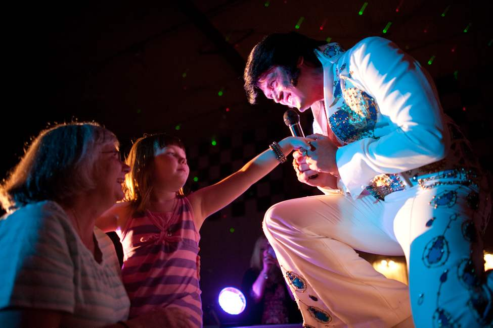 Corny Rempel, performing as Elvis, holds six-year-old Jett Zinck's hand after giving it a kiss at 11th annual Elvis Fest in Gimli, Manitoba. Elvis impersonators performed for a full Gimli recreation centre, which comes less than a week before the 35th anniversary of Elvis's death. COLE BREILAND / WINNIPEG FREE PRESS