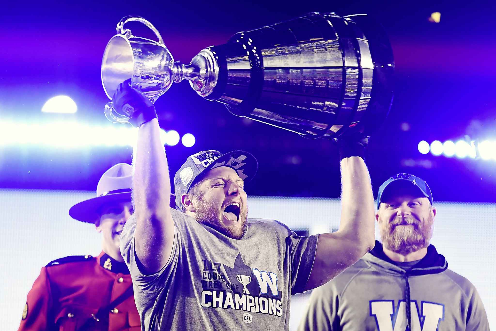 Winnipeg Blue Bombers' Jake Thomas lifts the Cup as head coach Mike O'Shea looks on as they celebrate winning the 107th Grey Cup against the Hamilton Tiger Cats in Calgary, Alta., Sunday, November 24, 2019. THE CANADIAN PRESS/Frank Gunn