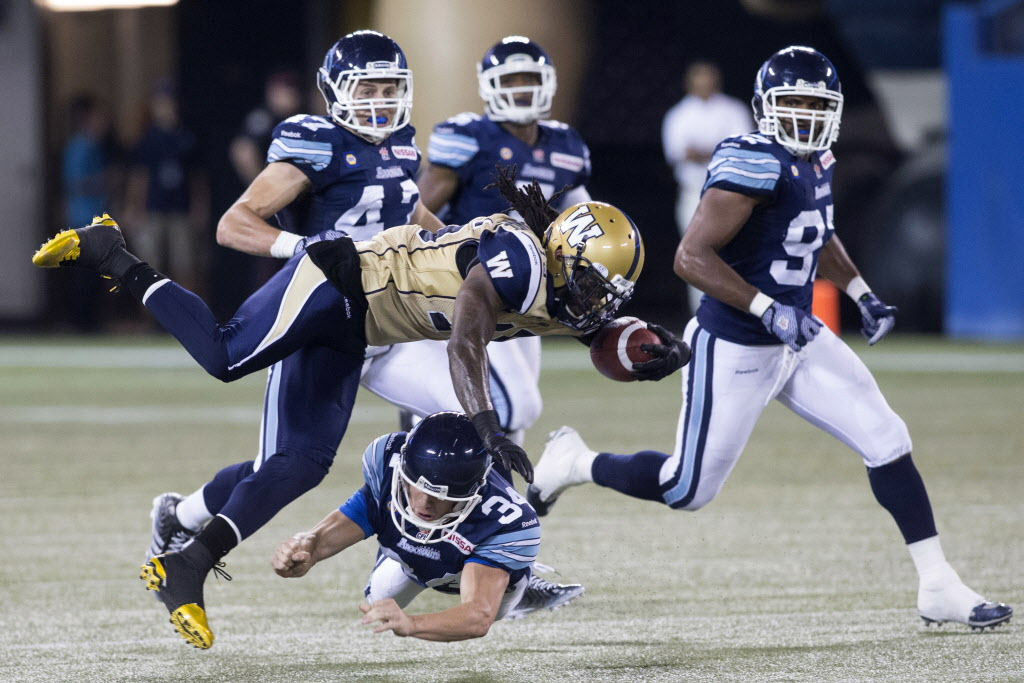 Winnipeg Blue Bombers defensive back Troy Stoudermire is tackled by Toronto Argonauts kicker Swayze Waters during the first half.