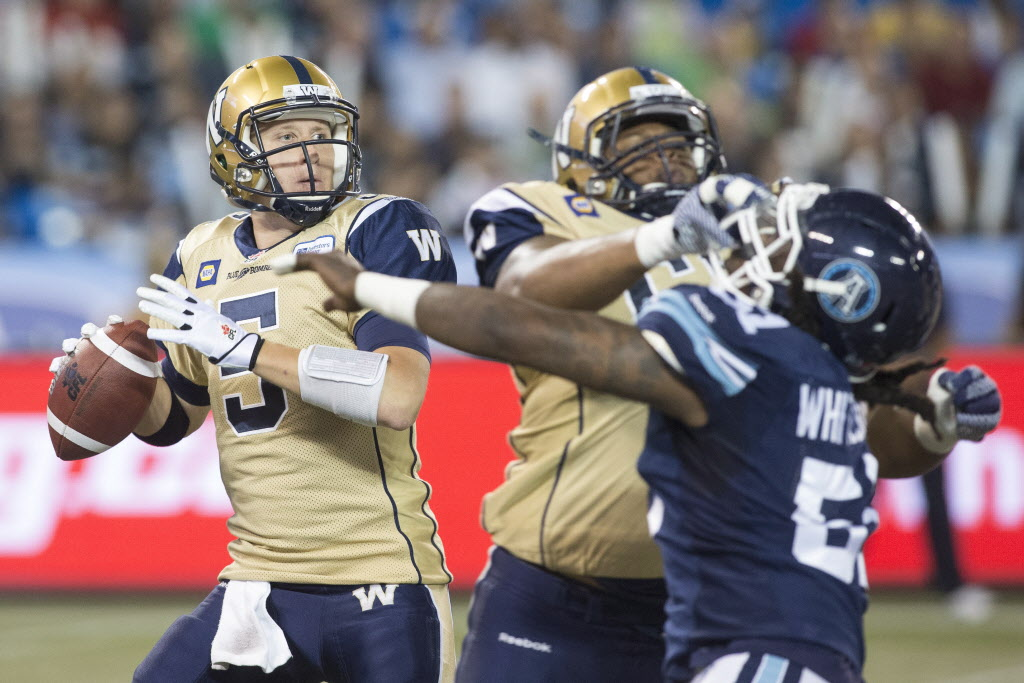 Winnipeg Blue Bombers quarter back Drew Willy (left) looks to make a play against Toronto Argonauts. (CP)