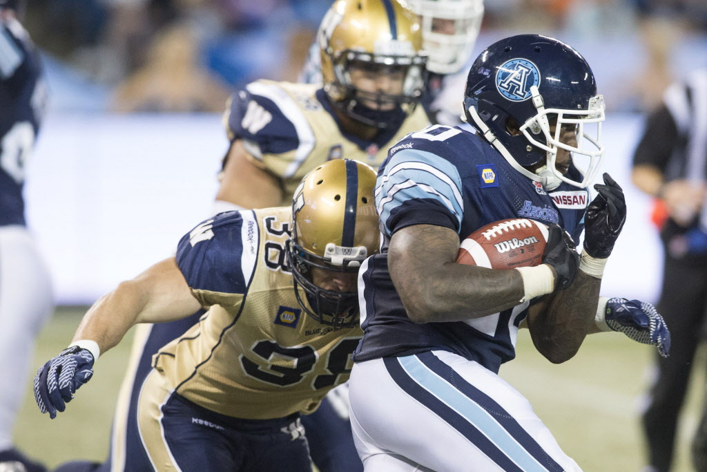 Toronto Argonauts running back Steve Slaton (right) breaks the tackle of Winnipeg Blue Bombers Ian Wild. (Chris Young / The Canadian Press)