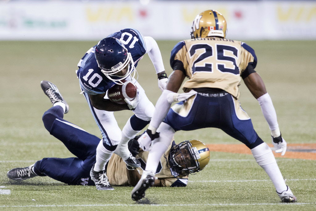Toronto Argonauts wide receiver Robert Gill (centre) is tackled by Winnipeg Blue Bombers defensive back Bruce Johnson. (Chris Young / The Canadian Press)