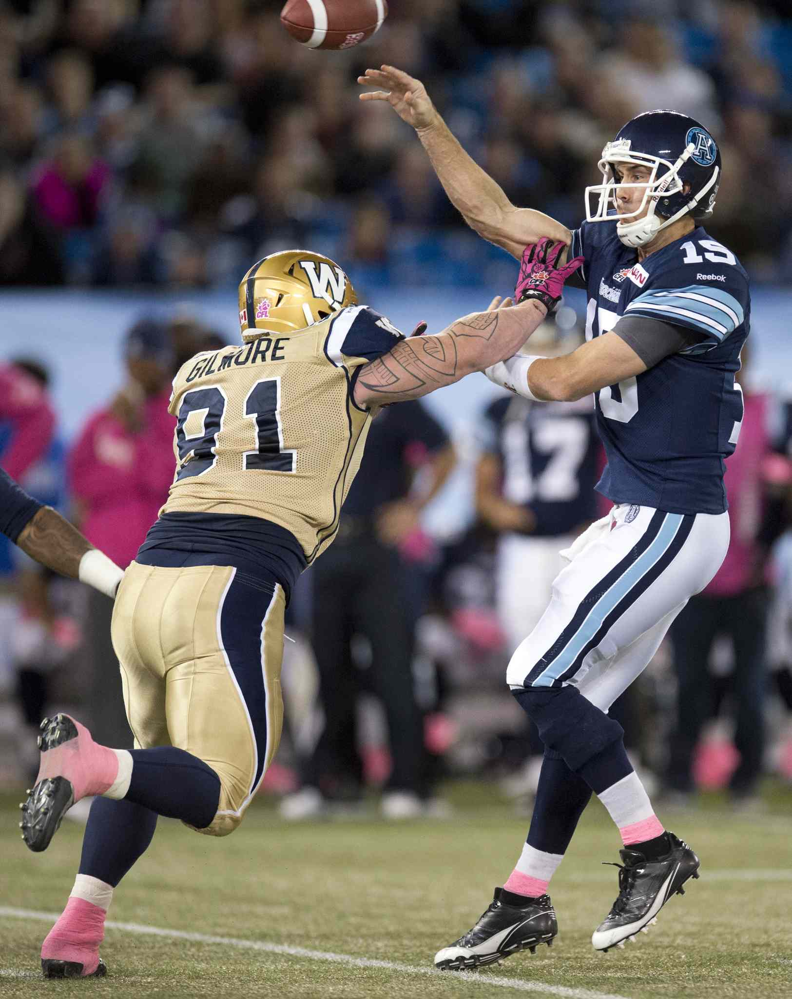 Toronto Argonauts quarterback Ricky Ray (right) dumps off a pass under pressure from Winnipeg Blue Bombers defensive tackle JT Gilmore during the first half.