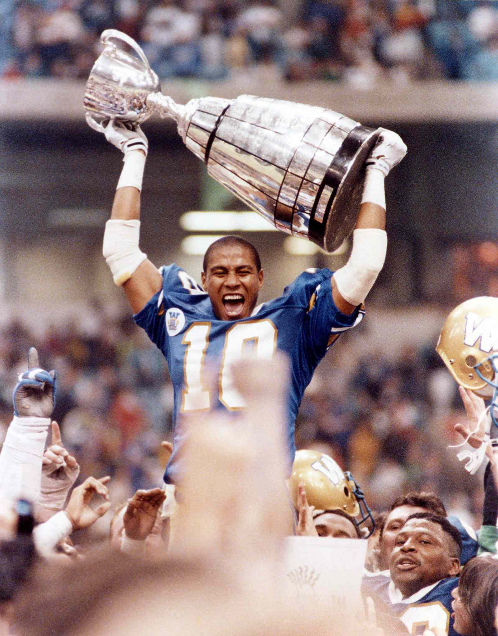 Winnipeg Blue Bombers' defensive back Rod Hill lets out a victory yell as he raises the Grey Cup over his head following the Bombers' 50-11 victory over the Edmonton Eskimos in Vancouver on November 25, 1990.