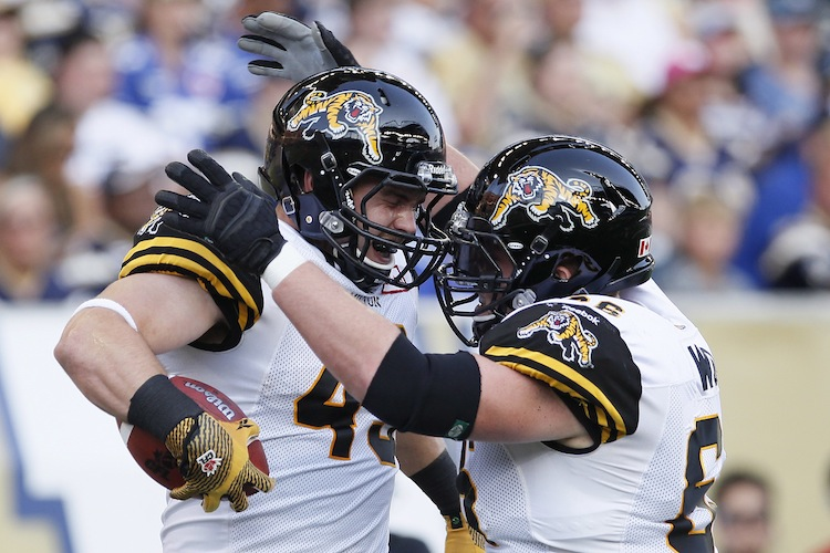 Hamilton Tiger-Cats' John Delahunt (49) and Greg Wojt (66) celebrate Delahunt's touchdown against the Winnipeg Blue Bombers during the first half.