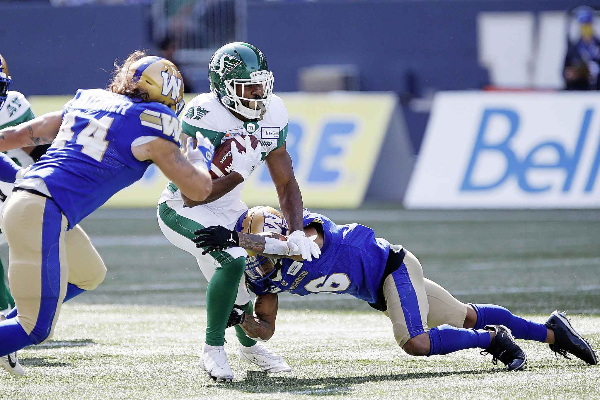 Winnipeg Blue Bombers' Mike Jones (16) tackled Saskatchewan Roughriders' William Powell (29) during the first half. (John Woods / The Canadian Press files)