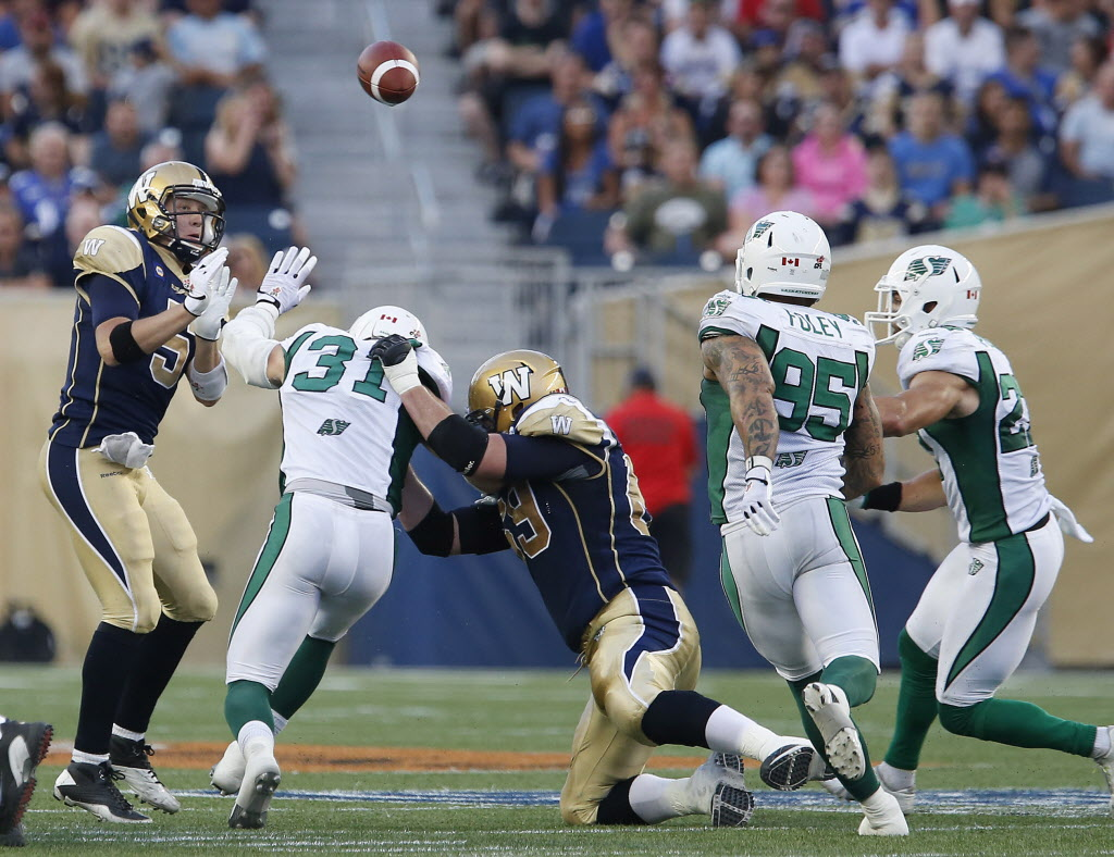 Winnipeg Blue Bombers' quarterback Drew Willy (5) gets the throw away despite pressure from Saskatchewan Roughriders' Samual Hurl (31) during the first half of the game.