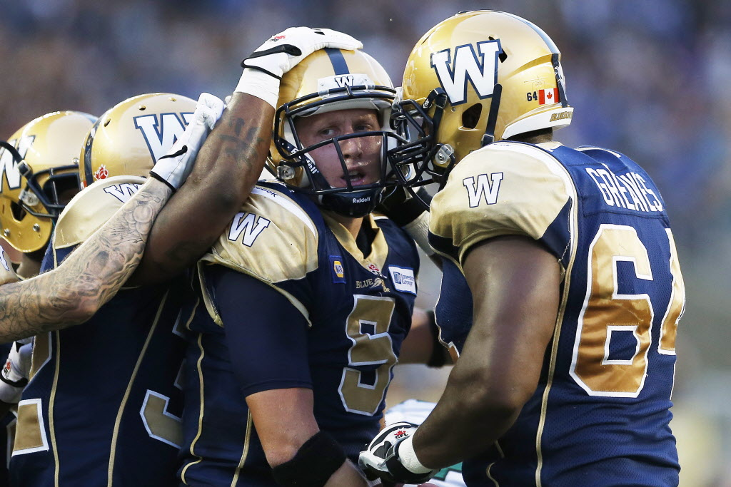 Winnipeg Blue Bombers' quarterback Drew Willy (5) celebrates his touchdown against the Saskatchewan Roughriders with Chris Greaves (64).