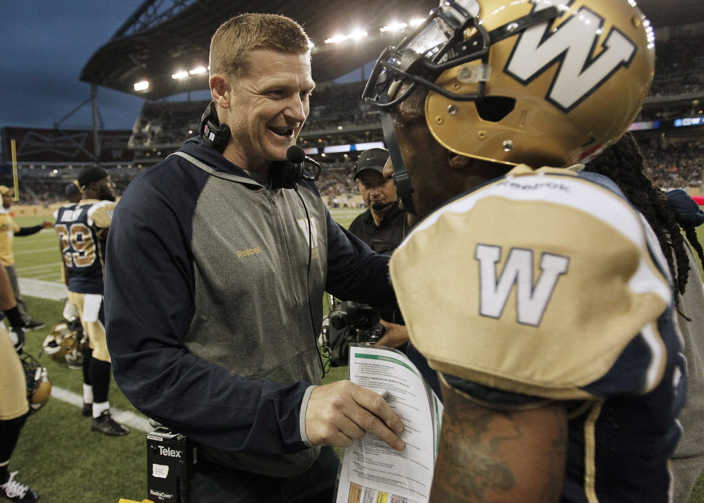 Winnipeg Blue Bombers head coach Mike O'Shea congratulates Demond Washington for his fumble recovery touchdown against the Toronto Argonauts. (John Woods / THE CANADIAN PRESS)
