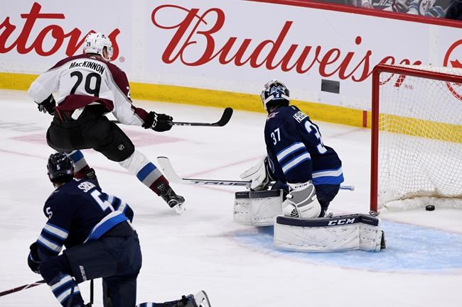 Colorado Avalanche's Nathan McKinnon (29) scores on Winnipeg Jets goaltender Connor Hellebuyck (37) during third period NHL action in Winnipeg on Tuesday, Nov. 12, 2019. THE CANADIAN PRESS/Fred Greenslade