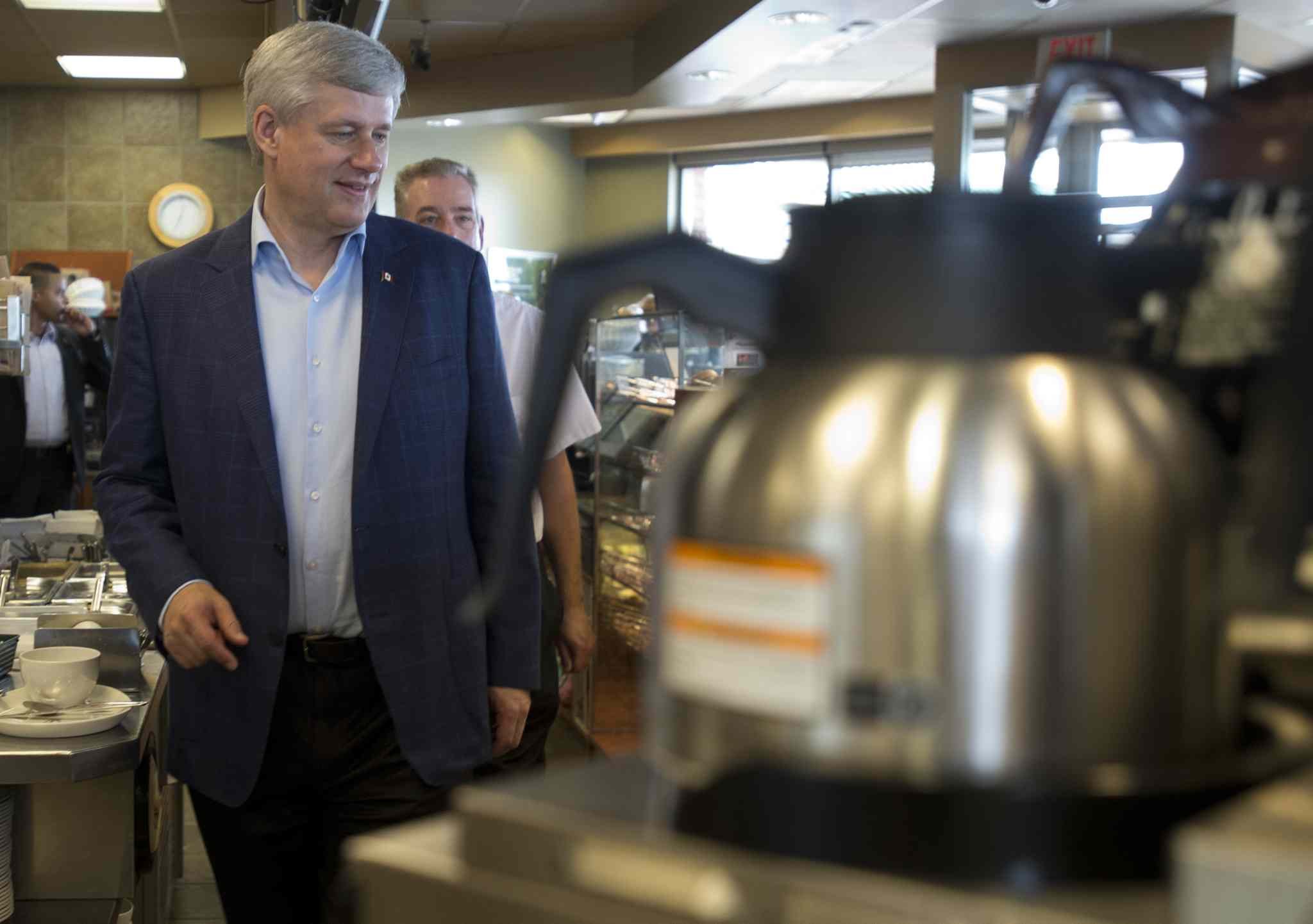 Conservative leader Stephen Harper walks behind the counter to serve coffee to supporters as he stops at a Tim Hortons in Gananoque, Ont., on Monday.