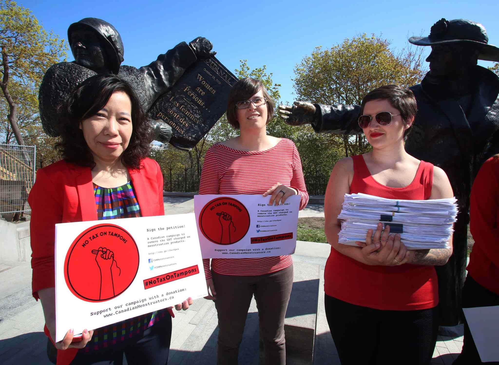 Lele Truong (from left), Lareen Jervis and Mariana Hollmann (left to right) take part in a news conference and petition on Parliament Hill in Ottawa earlier this month calling on the federal government to remove tax on feminine hygiene products.