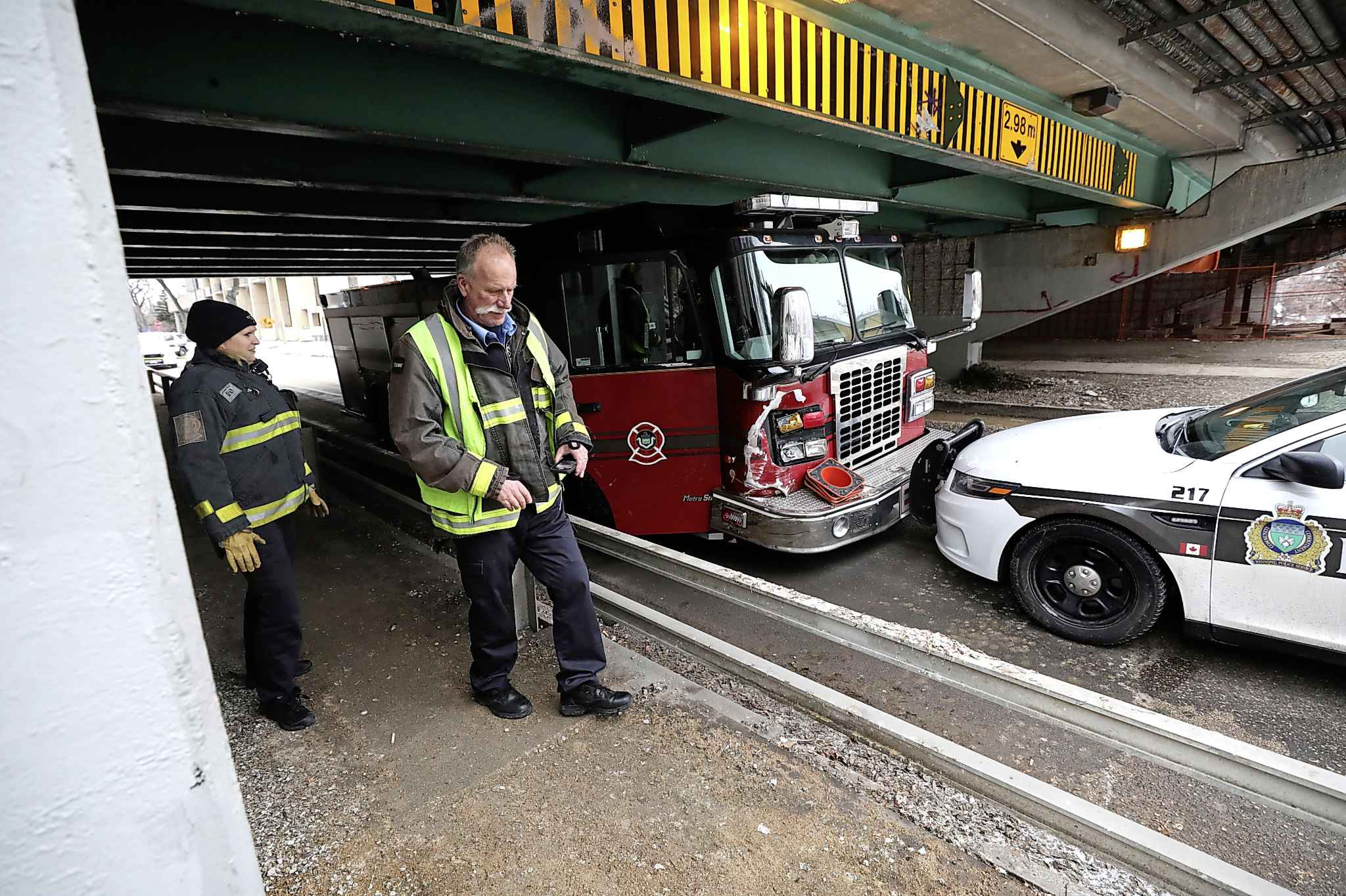 Winnipeg Police Officers and Fire Crews survey the damage on a stolen fire truck that was stopped by a police vehicle under the Donald Street Bridge on Assiniboine Ave., Friday.