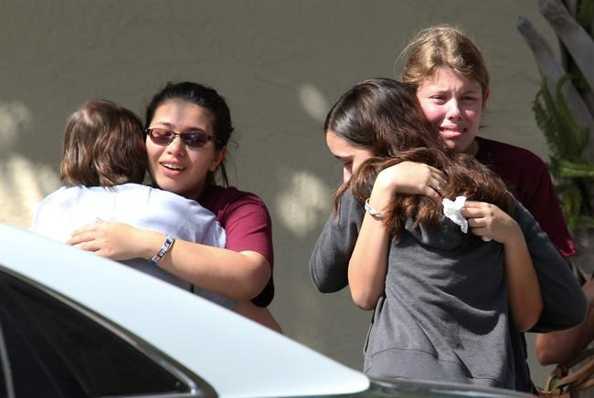 Students grieve outside Pines Trail Center where counselors are present, after Wednesday's mass shooting at Marjory Stoneman Douglas High School in Parkland, Fla., Thursday, Feb. 15, 2018. Nikolas Cruz was charged with 17 counts of premeditated murder Thursday morning. (AP Photo/Joel Auerbach)