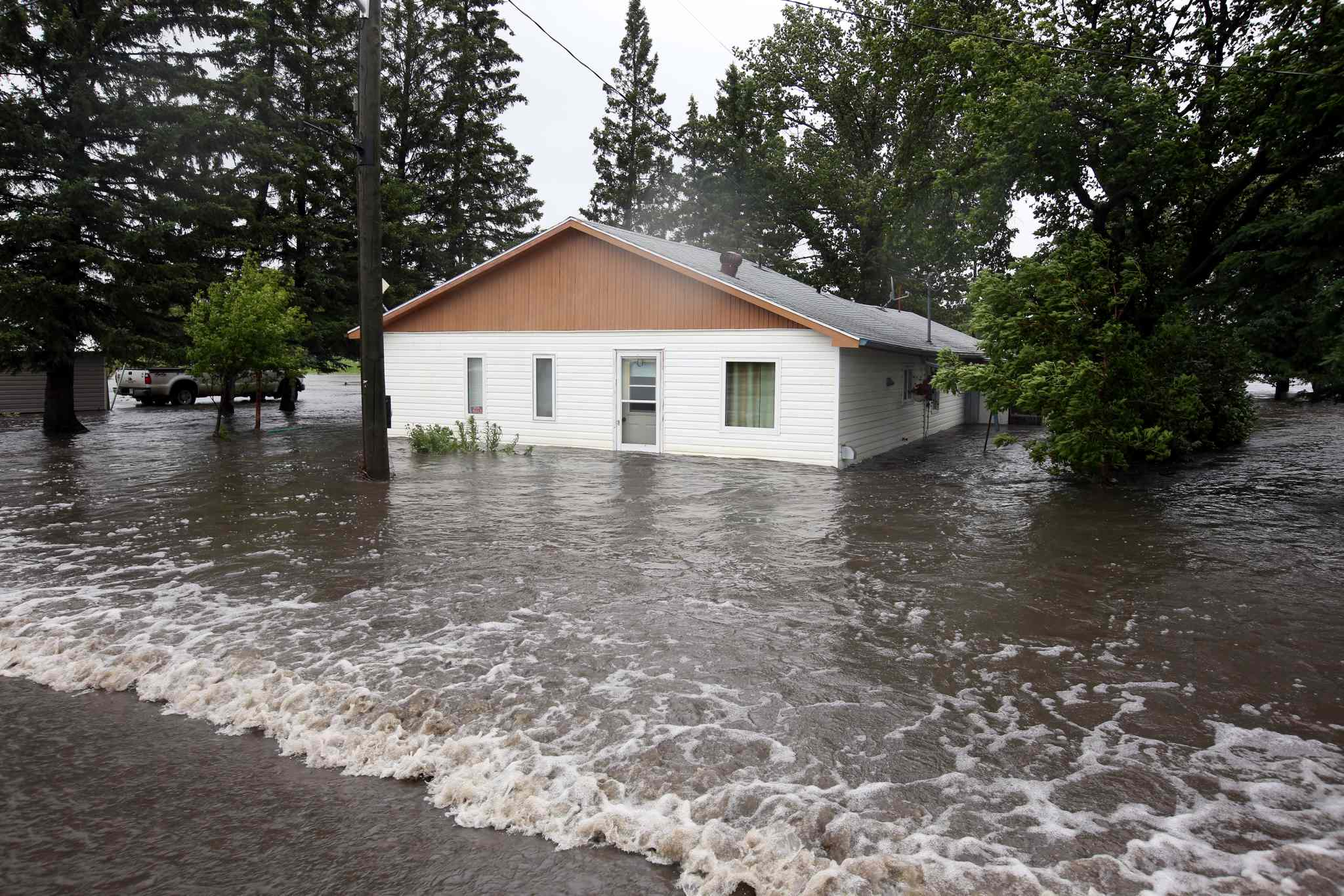 Water pours over Highway 256 and floods homes in the village of Cromer.