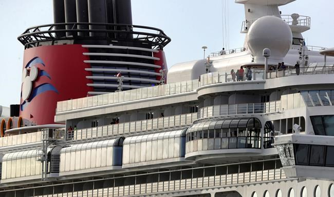 In this Monday, March 9, 2020 photo, the Disney Dream departs Port Canaveral, Fla. Disney Cruise Line announced that after Saturday, March 14, all of their cruises will suspend operations through the end of the month in response to the coronavirus threat. (Joe Burbank/Orlando Sentinel via AP)