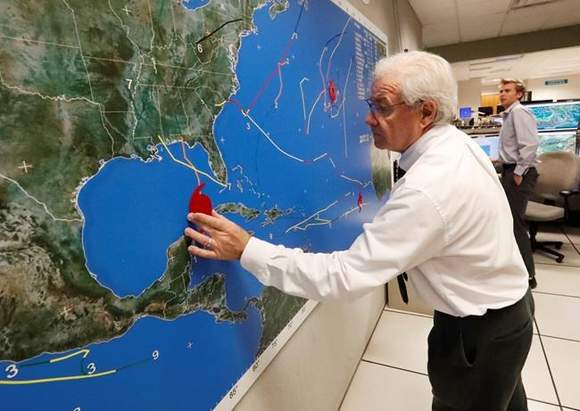 National Oceanic and Atmospheric Administration public affairs officer Dennis Feltgen updates the progress of Hurricane Michael on a large map, Tuesday, Oct. 9, 2018, at the Hurricane Center in Miami. At least 120,000 people along the Florida Panhandle were ordered to clear out Tuesday as Hurricane Michael rapidly picked up steam in the Gulf of Mexico and closed in with winds of 110 mph (175 kph) and a potential storm surge of 12 feet (3.7 meters). (AP Photo/Wilfredo Lee)