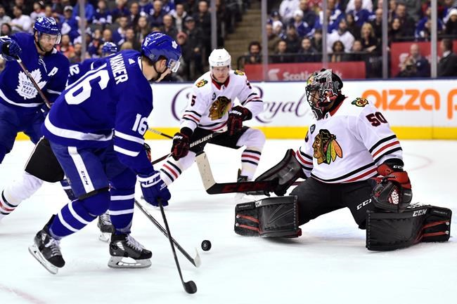 Toronto Maple Leafs right wing Mitchell Marner (16) looks to control a pass as Chicago Blackhawks goaltender Corey Crawford (50) covers his net during first period NHL hockey action in Toronto on Wednesday, March 13, 2019. THE CANADIAN PRESS/Frank Gunn