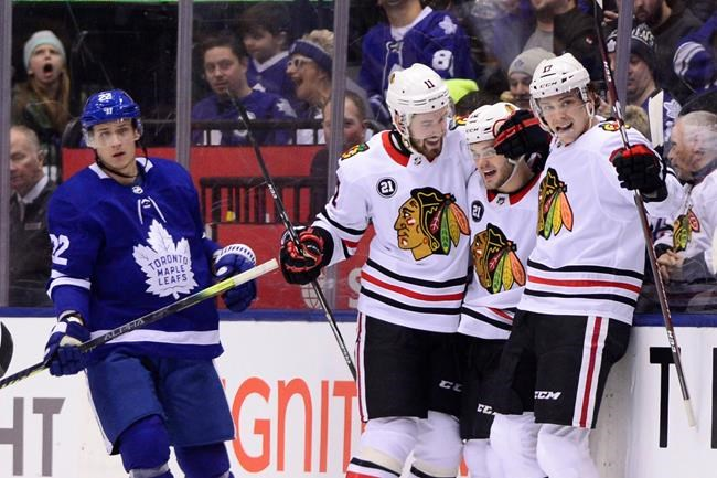Chicago Blackhawks left wing Alex DeBrincat (12) celebrates his goal with teammates Chicago Blackhawks left wing Brendan Perlini (11) and Chicago Blackhawks centre Dylan Strome (17) as Toronto Maple Leafs defenceman Nikita Zaitsev (22) skates pass during second period NHL hockey action in Toronto on Wednesday, March 13, 2019. THE CANADIAN PRESS/Frank Gunn