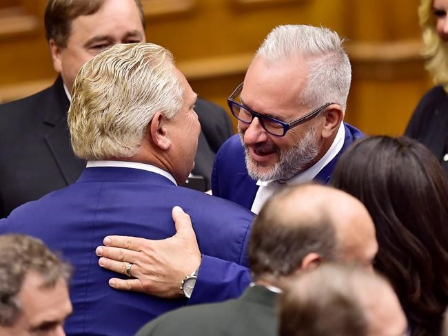Ontario Premier Doug Ford, left, get a hug from Toronto Police Association president Mike McCormack following the speech from the throne by Lt.-Gov. Elizabeth Dowdeswell to open the new legislative session at the Ontario Legislature at Queen's Park in Toronto on Thursday, June 12, 2018. THE CANADIAN PRESS/Frank Gunn