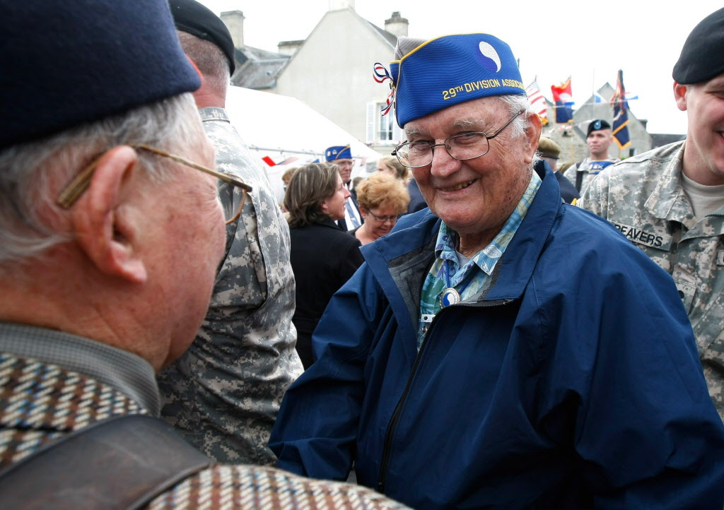 Eighty nine year old U.S. WW II veteran Joseph Steimel from Indianapolis, Indiana, who landed at the Omaha Beach, on July, 1944 with the 29th Infantry Division, shakes hands with French Veterans, during a a ceremony in honor of the division, in La Cambe, France, as part of the commemoration of the 70th D-Day anniversary on Wednesday.