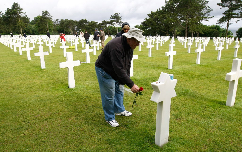 Thomas Herman, 67, from New York, USA., places a flower on the grave of Joseph Feinberg, in the Normandy American Cemetery and Memorial, in Colleville sur Mer, France on Wednesday.