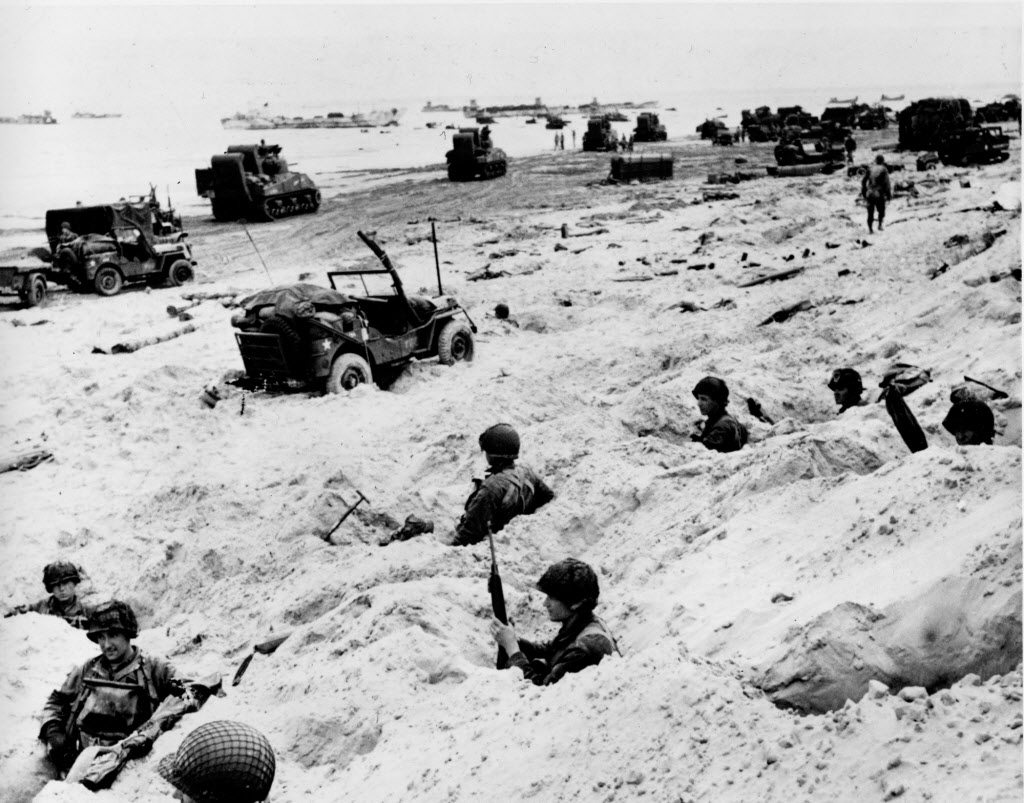American soldiers of the Allied Expeditionary Force securing a beachhead during initial landing operations at Normandy, France, June 6, 1944.