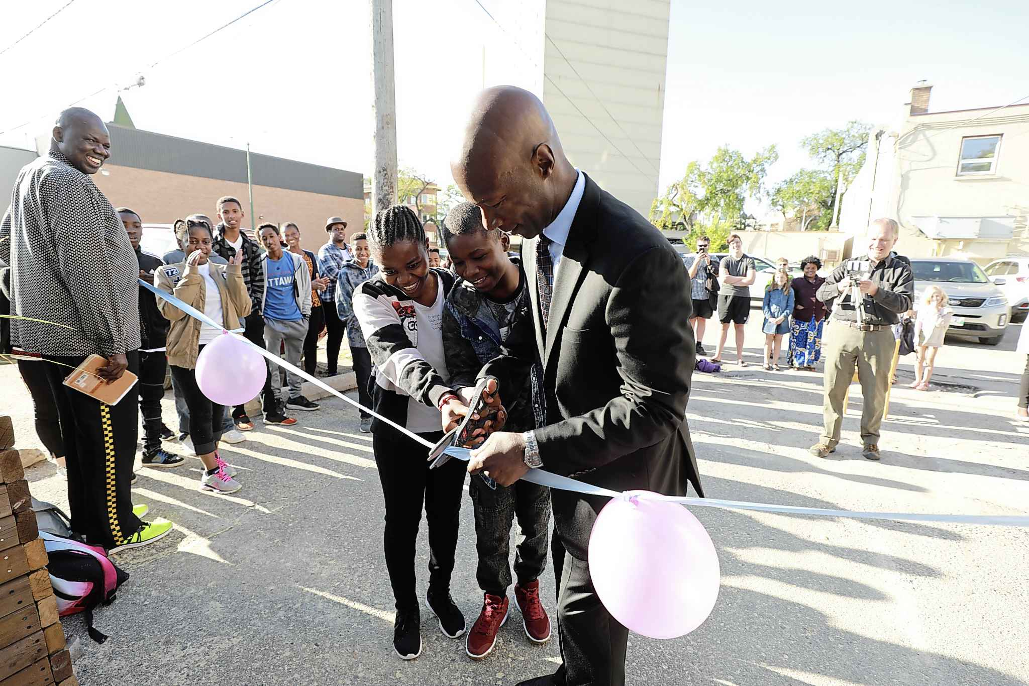 Former City of Winnipeg Police Chief, Devon Clunis, and students, Christina Dusabimana, left, and Gervas Kezimana, cut the ribbon before students enter school for the first day Wednesday.