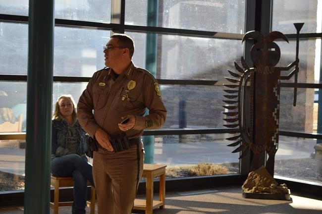 A San Juan County Sheriff's deputy prepares for a press conference in Aztec, N.M. on Thursday, Dec. 7, 2017, after a school shooting at the city's high school. Students hid in their classrooms, some behind locked doors, as a suspect opened fire Thursday inside Aztec High School, killing two classmates before ending up dead. (AP Photo/Russell Contreras)