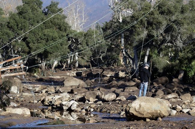 A man stands near downed power lines in Montecito, Calif., Wednesday, Jan. 10, 2018. Dozens of homes were swept away or heavily damaged and several people were killed Tuesday as downpours sent mud and boulders roaring down hills stripped of vegetation by a gigantic wildfire that raged in Southern California last month. (AP Photo/Marcio Jose Sanchez)