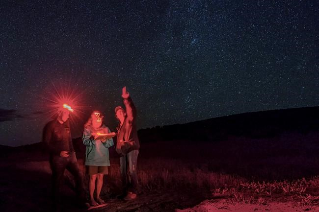 """In this July 15, 2018 photo provided by Kurt Kuznicki, people stargaze in the Massacre Rim Wilderness Area in northwestern Nevada, 150 miles north of Reno and near the state line with Oregon. Massacre Rim is one of two areas designated as """"dark sky sanctuaries"""" in Nevada. A bill passed by the Nevada state Senate would create a state program to encourage tourism and preservation of dark sky places. (Kurt Kuznicki via AP)"""