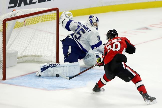Ottawa Senators centre Vladislav Namestnikov (90) gets his stick on the puck to score as Tampa Bay Lightning goaltender Curtis McElhinney (35) tries to defend during third period NHL hockey action in Ottawa, Saturday, Oct. 12, 2019. THE CANADIAN PRESS/Fred Chartrand