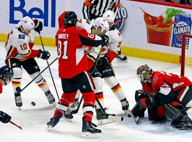 Ottawa Senators goaltender Marcus Hogberg (35) prepares to stop a shot from Calgary Flames centre Derek Ryan (10) as Ottawa Senators defenceman Ron Hainsey (81)defends against Calgary Flames left wing Milan Lucic (17) and Calgary Flames centre Elias Lindholm (28) during third period NHL hockey action in Ottawa, Saturday, Jan. 18, 2020. THE CANADIAN PRESS/Fred Chartrand