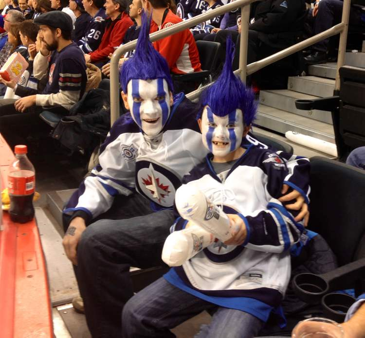 Jets fans show their true colours Saturday afternoon inside the MTS Centre as the Jets host the Ottawa Senators. (Boris Minkevich / Winnipeg Free Press)