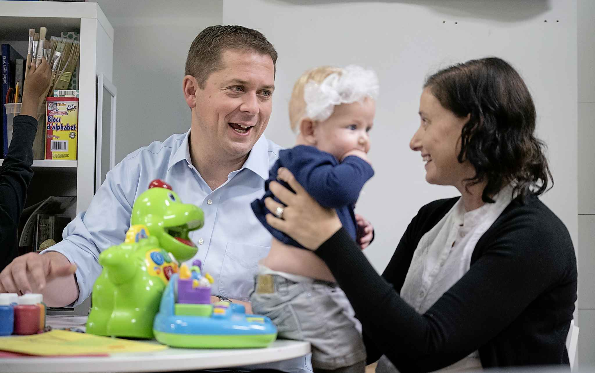 Conservative leader Andrew Scheer chats with a mother holding her child while visiting a daycare in Toronto, on Thursday.
