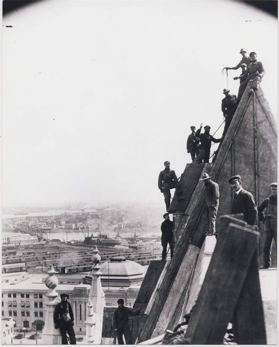 Construction crews install copper sheathing onto the roof of the Fort Garry Hotel in Winnipeg. Dated 1912-13.