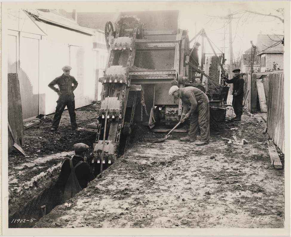 A labour crew digs a trench for steam pipes in the North End of Winnipeg, October 21, 1930.