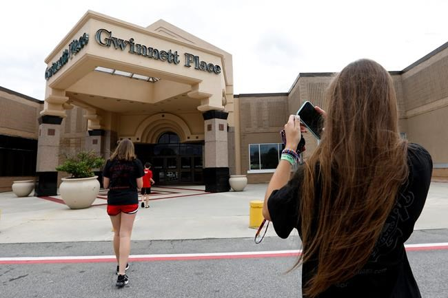 In this Tuesday, July 23, 2019 photo, Brinley Rawson, a 17-year-old Stranger Things fan from Gwinnett County, snaps a photo of Gwinnett Place Mall in Duluth, Ga. Stranger Things filmed much of season three at the mall, which was called Starcourt Mall in the show. (AP Photo/Andrea Smith)