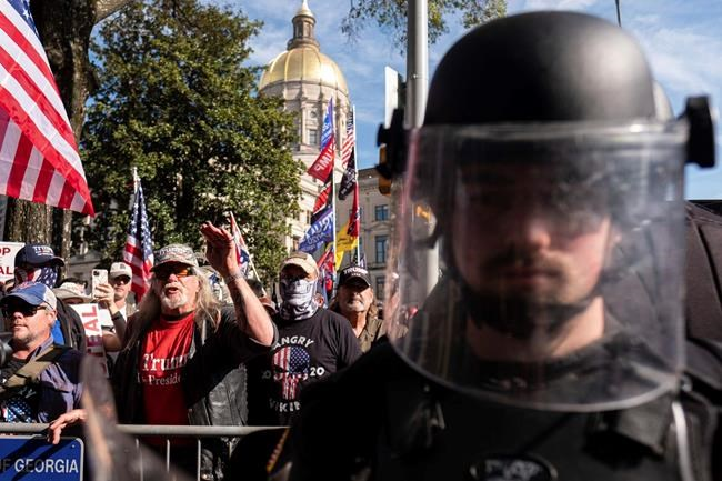 An officer in riot gear stands between supporters of President Donald Trump and counter protesters as the groups yell at each other outside of the Georgia State Capitol in Atlanta on Saturday, Nov. 21, 2020. (AP Photo/Ben Gray)