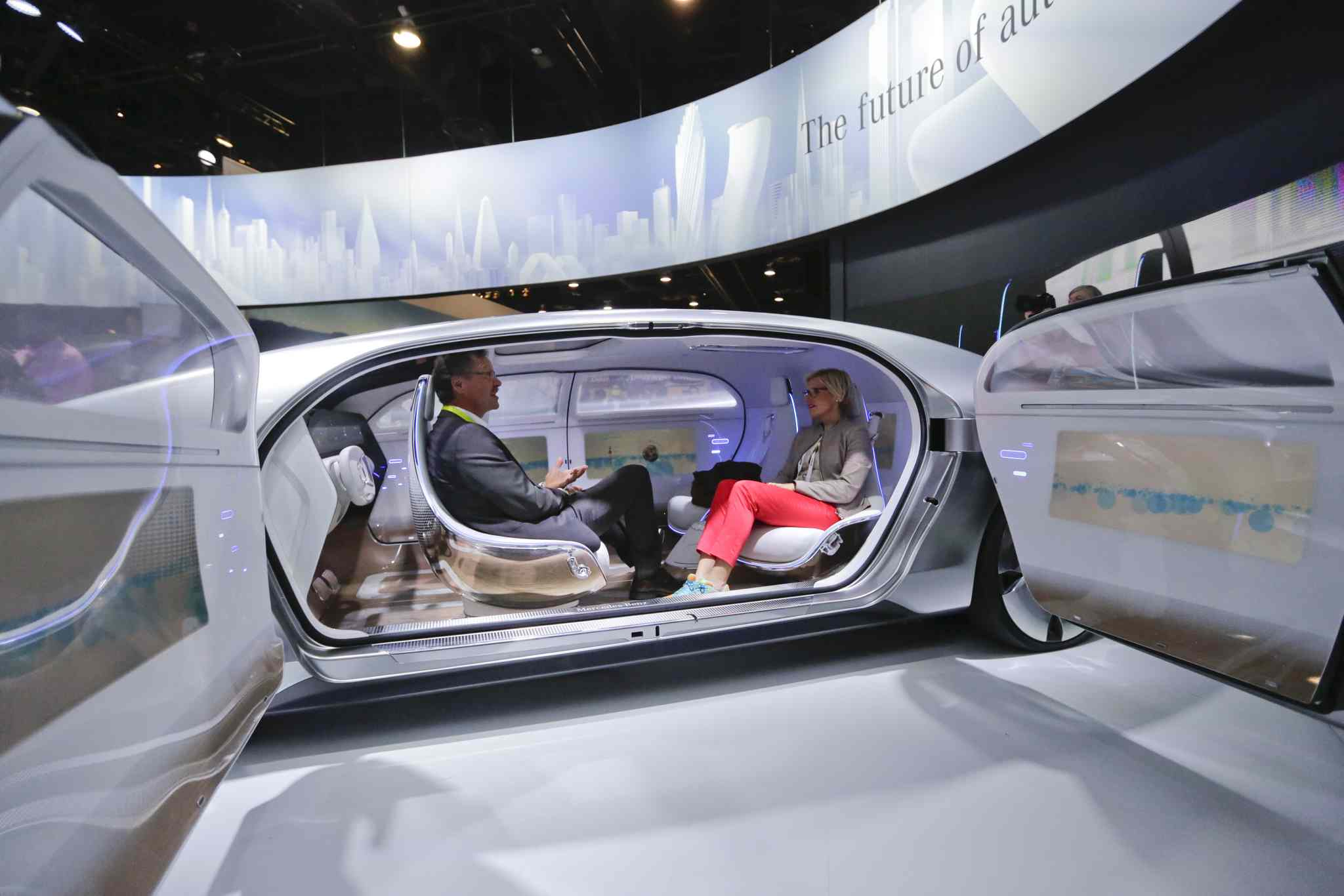Attendees sit in the self-driving Mercedes-Benz F 015 concept car at the Mercedes-Benz booth at the International CES in January.