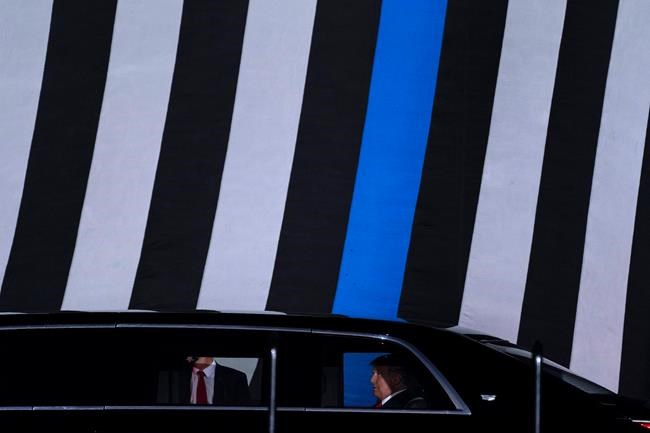 "With a ""Thin Blue Line"" flag in the background, President Donald Trump arrives to speak to a campaign rally at Middle Georgia Regional Airport, Friday, Oct. 16, 2020, in Macon, Ga. (AP Photo/Evan Vucci)"