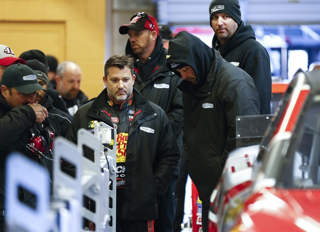 NASCAR driver and team owner Tony Stewart, center, and crew members watch a car go through tech inspection during qualifying for Sunday's NASCAR Sprint Cup Series auto race Friday, Feb. 27, 2015, in Hampton, Ga. Thirteen drivers did not get on the track after failing to pass inspection, Stewart included. (AP Photo/John Bazemore)