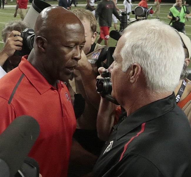 Tampa Bay Buccaneers head coach Lovie Smith, left, speaks with Atlanta Falcons head coach Mike Smith after the second half of an NFL football game, Thursday, Sept. 18, 2014, in Atlanta. The Atlanta Falcons won 56-14.(AP Photo/John Bazemore)