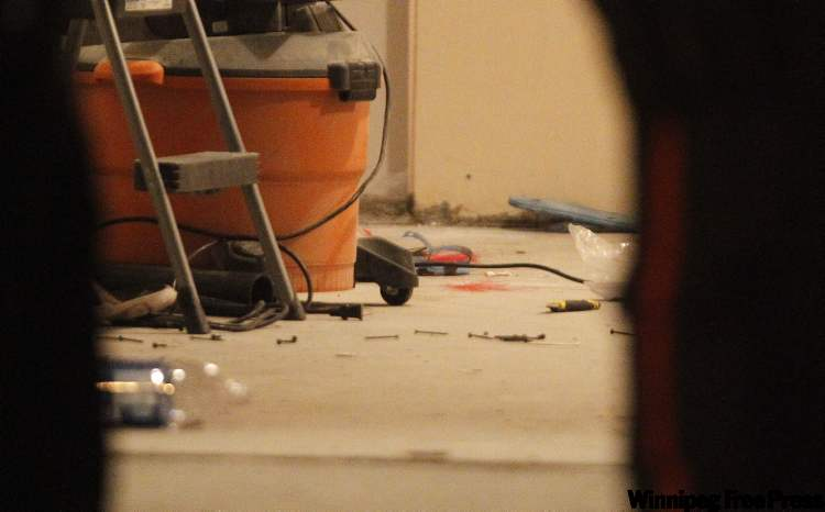 Blood on the floor inside the garage of 39 Lou Peltier Crescent after a triple shooting.
