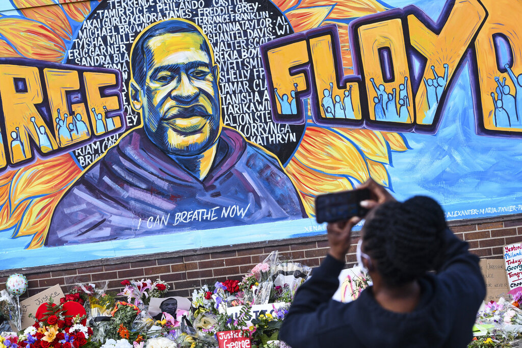 A person photographs a mural in memory of George Floyd in Minneapolis. Floyd died while in Minneapolis police custody and protests have erupted across the United States after video was released showing a Minneapolis Police officer kneeling on his neck while he was handcuffed and pleading that he could not breathe. (Dave Schwarz/St. Cloud Times via AP)