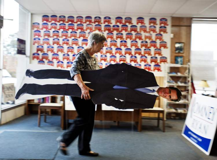 Volunteer Clare Frew puts away a life-size cut out of presidential hopeful Mitt Romney as she prepares to close the Chatham County Republican Campaign office, Tuesday, in Savannah, Ga. After a grinding presidential campaign, Americans are heading into polling places across the country.  (Stephen Morton / The Associated Press)