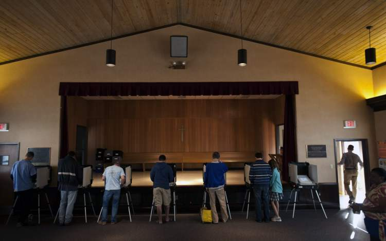 Voters in one of the county's busiest precincts cast their ballots in front of the stage at the First Presbyterian Church, Tuesday, , in Savannah, Ga.  (Stephen Morton / The Associated Press)